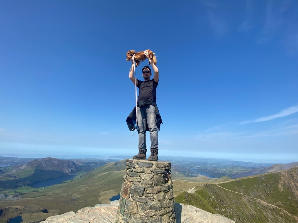 Aaron holds Chester in the air stood on top of the summit marker of Mt Snowdon